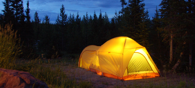 Glowing tent at night in the wilderness
