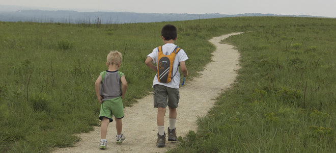 Two children traveling on a walking trail in manhattan ks